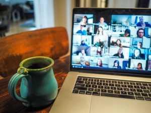 Imagen con una pantalla de ordenador donde se ven varias caras: es una videollamada o evento online.
