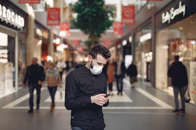 Hombre con mascarilla que utiliza un smartphone.