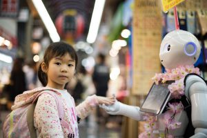 Nena asiàtica saludant un robot.